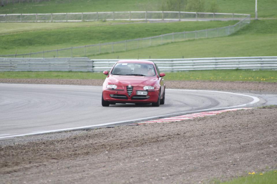 Röd Alfa Romeo 147 i en kurva på racerbanan Gelleråsen