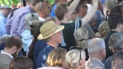 En man i hatt lyssnar till partiledartal i Almedalen.