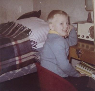 En femårig pojke sitter framför en radio med huvudet stött i handen och armbågen på bordet som radion står på.